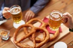 Schließen Sie oben von den Händen mit den Bierkrügen an der Bar oder an der Kneipe Lizenzfreie Stockbilder