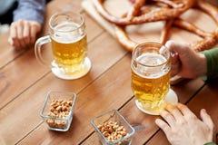Schließen Sie oben von den Händen mit den Bierkrügen an der Bar oder an der Kneipe Lizenzfreie Stockfotos