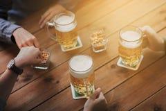 Schließen Sie oben von den Händen mit den Bierkrügen an der Bar oder an der Kneipe Stockbild