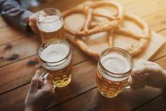 Schließen Sie oben von den Händen mit den Bierkrügen an der Bar oder an der Kneipe Lizenzfreies Stockfoto