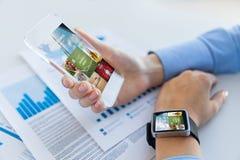 Schließen Sie oben von den Händen mit intelligentem Telefon und Uhr Lizenzfreies Stockfoto