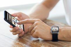 Schließen Sie oben von den Händen mit intelligentem Telefon und Uhr Stockfotos