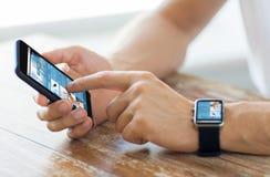 Schließen Sie oben von den Händen mit intelligentem Telefon und Uhr Lizenzfreie Stockbilder