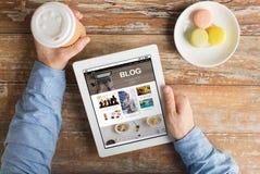 Schließen Sie oben von den Händen mit Internet-Blog auf Tabletten-PC Stockfotos