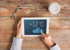 Schließen Sie oben von den Händen mit metcast auf Tabletten-PC-Schirm Lizenzfreie Stockfotos