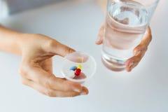 Schließen Sie oben von den Händen mit Pillen und vom Glas Wasser Stockbilder
