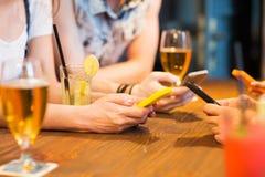 Schließen Sie oben von den Händen mit Smartphones an der Stange Lizenzfreie Stockfotografie