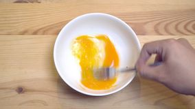Schließen Sie oben von den Händen schlagen Ei in einer weißen Schüssel, um Omelett zuzubereiten stock footage