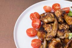 Schließen Sie oben von den Hühnerflügeln, die mit Honig und Tomaten gebraten werden stockbild