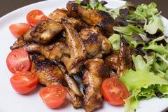 Schließen Sie oben von den Hühnerflügeln, die mit Honig verzierten Tomaten gebraten werden stockfoto