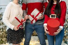 Schließen Sie oben von den jungen Leuten in den Strickjacken, die Geschenke halten lizenzfreie stockbilder