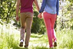 Schließen Sie oben von den jungen Paaren, die in Sommer-Landschaft gehen Stockfotografie