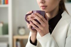 Schließen Sie oben von den jungen Schönheitshänden, die heiße Schale coffe halten Stockfoto