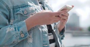 Schließen Sie oben von den jungen weiblichen Händen unter Verwendung des Telefons, draußen stock footage