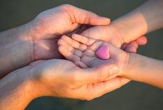 Schließen Sie oben von den Kinder- und Mannhänden mit Herzen Stockbild