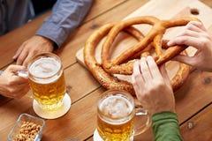 Schließen Sie oben von den Männern, die Bier mit Brezeln an der Kneipe trinken Lizenzfreie Stockfotografie