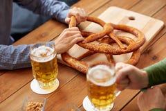 Schließen Sie oben von den Männern, die Bier mit Brezeln an der Kneipe trinken Stockfotos