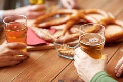 Schließen Sie oben von den Männern, die Bier mit Brezeln an der Kneipe trinken Lizenzfreie Stockbilder