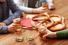 Schließen Sie oben von den Männern, die Bier mit Brezeln an der Kneipe trinken Stockbild