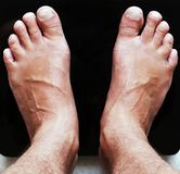 Schließen Sie oben von den männlichen Füßen auf Glasskalen des schwarzen digitalen Bodens lizenzfreies stockfoto