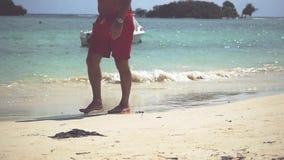 Schließen Sie oben von den männlichen Füßen, die auf goldenen Sand am Strand mit Meereswogen gehen Sommer-Ferien-Feiertag Langsam stock video
