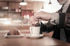 Schließen Sie oben von den männlichen Händen, dass, Zucker addierend stockbilder