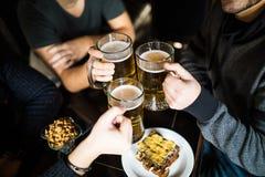 Schließen Sie oben von den männlichen Händen, die Biergläser an der Bar oder an der Kneipe klirren stockbild