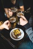 Schließen Sie oben von den männlichen Händen, die Biergläser an der Bar oder an der Kneipe klirren stockfotografie
