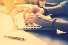 Schließen Sie oben von den männlichen Händen, die an Laptop auf seinem Schreibtisch arbeiten Lizenzfreie Stockfotografie