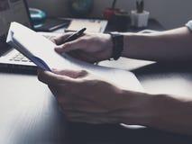 Schließen Sie oben von den männlichen Händen halten Papier mit Stift auf seinem Schreibtisch Lizenzfreies Stockbild