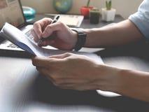 Schließen Sie oben von den männlichen Händen halten Papier mit Stift auf seinem Schreibtisch Lizenzfreie Stockbilder