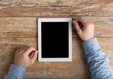 Schließen Sie oben von den männlichen Händen tablet PC auf Tabelle Lizenzfreie Stockfotos