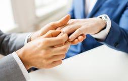 Schließen Sie oben von den männlichen homosexuellen Paarhänden und -Ehering lizenzfreie stockbilder
