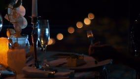 Schließen Sie oben von den Mannhänden, die einen Nachtisch auf dem Datum durch Kerzenlicht nachts essen stock video footage