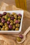 Schließen Sie oben von den Oliven mit dem Rosmarin, der in der Schüssel auf Papier gedient wird Lizenzfreie Stockfotografie