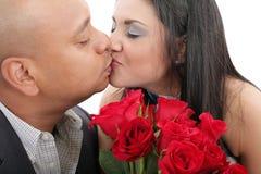 Schließen Sie oben von den Paaren, die einen Blumenstrauß von roten Rosen halten küssen Stockbilder