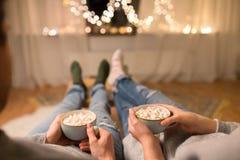 Schließen Sie oben von den Paaren, die zu Hause heiße Schokolade trinken stockfotos
