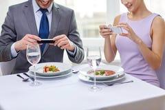 Schließen Sie oben von den Paaren mit Smartphones am Restaurant Stockfotos