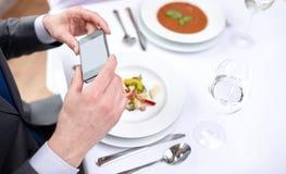 Schließen Sie oben von den Paaren mit Smartphones am Restaurant Lizenzfreies Stockfoto