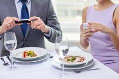 Schließen Sie oben von den Paaren mit Smartphones am Restaurant Lizenzfreie Stockbilder