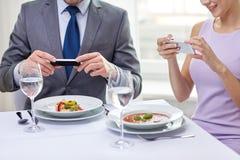 Schließen Sie oben von den Paaren mit Smartphones am Restaurant Lizenzfreie Stockfotos