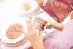 Schließen Sie oben von den Paaren mit Smartphones am Restaurant Stockfotografie