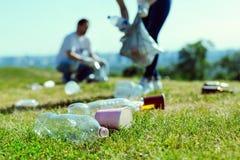 Schließen Sie oben von den Plastikflaschen dieses Lügen auf dem Gras Lizenzfreie Stockfotos