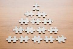 Schließen Sie oben von den Puzzlespielstücken auf Holzoberfläche Stockfoto