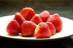 Schließen Sie oben von den reifen Erdbeeren auf weißer Platte. stockfotografie