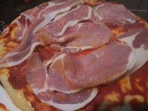 Schließen Sie oben von den rohen Speckstreifen auf einer ungekochten Pizza Stockbild