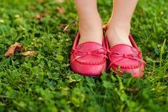 Schließen Sie oben von den roten Mokassinen auf den Füßen des Kindes Lizenzfreie Stockfotografie