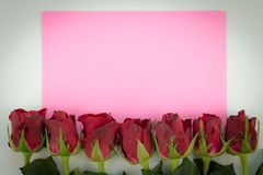 Schließen Sie oben von den roten Rosen auf einem hölzernen Hintergrund mit leerem Mitteilungs-Zeichen für Ihren Text oder Mitteil Lizenzfreies Stockbild