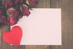 Schließen Sie oben von den roten Rosen und vom roten Herzen auf einem hölzernen Hintergrund mit leerem Mitteilungs-Zeichen für Ih Stockfoto
