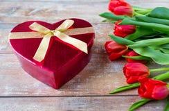 Schließen Sie oben von den roten Tulpen und von der Pralinenschachtel Stockfoto